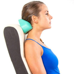 Woman using the Original CranioCradle device on neck sitting in chair.