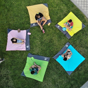 5 kids, each sitting on a different colored pocket blanket, in a circle on the grass.