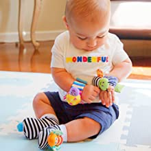 baby playing with wrist rattle bug