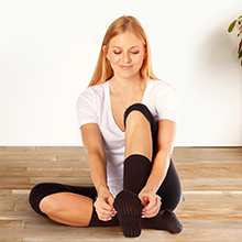 Woman sitting at house on floor putting on crew grip sock