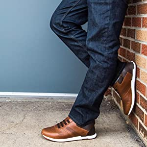 Image of a man wearing jeans and a pair of stylish brown Kizik shoes while leaning against a wall.