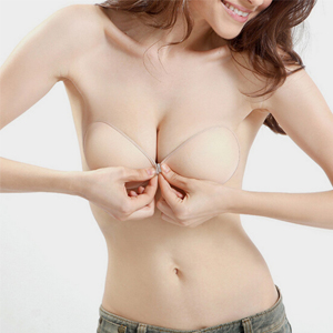 woman is putting on an adhesive bra
