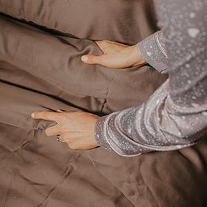 Woman in pajamas pulls back Samp;G duvet and comforter combo