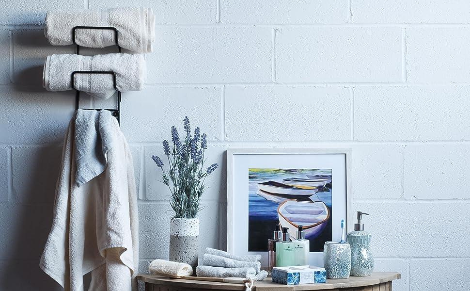 towel rack towels shampoo bath essentials picture frame lavender fake plants washcloths soap