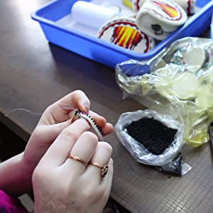 Image show a women Beading tiny beads on a thread for making fringes