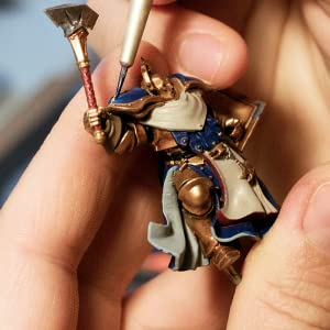 painting warhammer figurine with brush