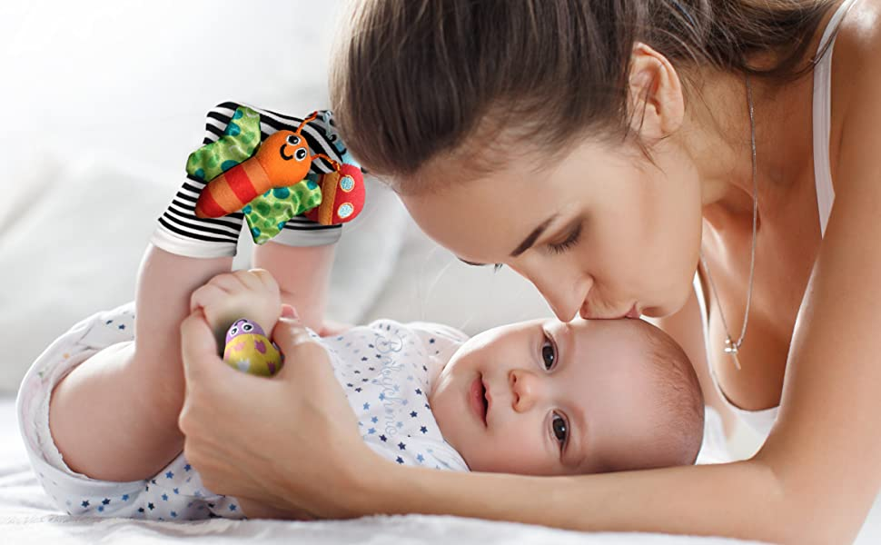 Mother kissing baby on forehead. Baby wearing Babychino rattle socks and wrist rattles toy