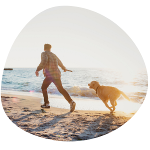Man and Healthy Dog Running and Playing on the Beach