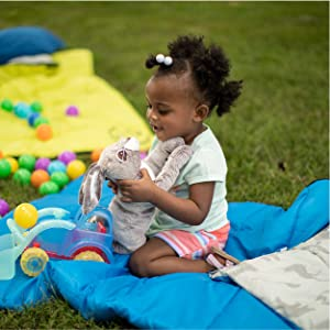 Young girl playing with toys on blue youth camp bag