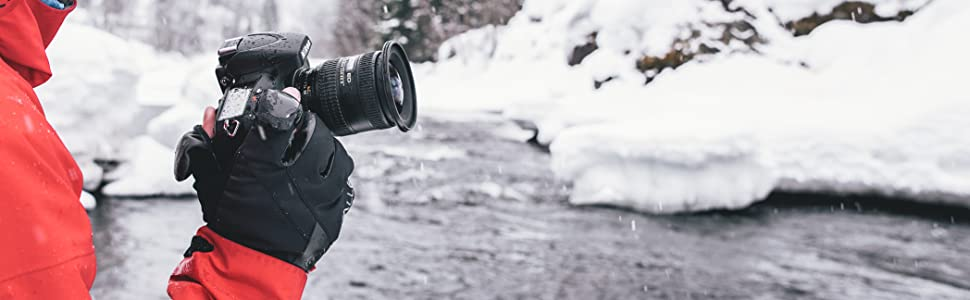 Photography gloves and man holding camera near snowy river