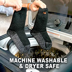 Two hands with bracelets holding black socks while placing over to go inside the washing machine.