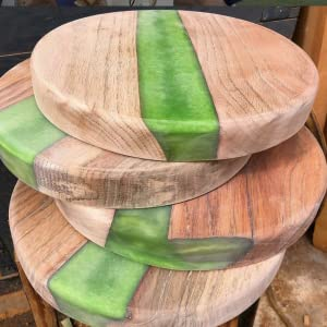 A stack of wooden round tables with a green thick pour at the center ideal as a coffee table corner