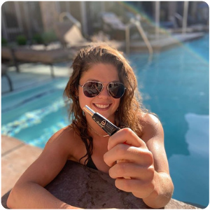 A woman in the pool holding her Aubio Cold Sore Treatment Gel