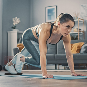 Woman using black Limm Core Sliders for mountain climbers exercise
