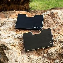 black and titanium coloured aluminium credit card holder wallet on the ground