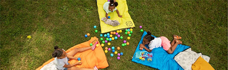Girls sitting and laying on sleeping bags in grass with colored balls and toys