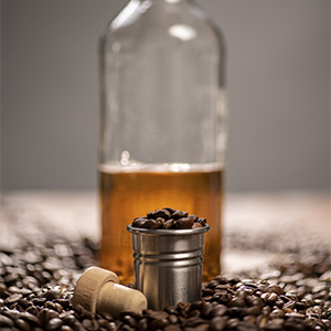 [Image of a glass or bottle of dark rum and whole coffee beans