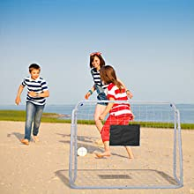 3 kids playing soccer with soccer goal on the beach