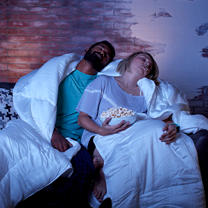 Cozy couple falls asleep on couch wrapped in Sheets amp; Giggles Comforter