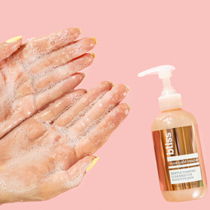 hands lathering with rose gold bottle next to it.