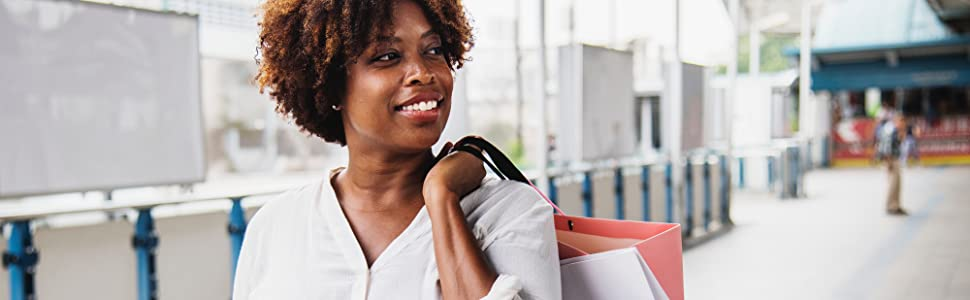 woman smiling and holding bags over shoulder