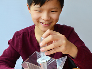 Boy assembling Party Lamp Kit plastic housing parts and PCB and LED electronics