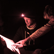 Men looking at map at night with red light