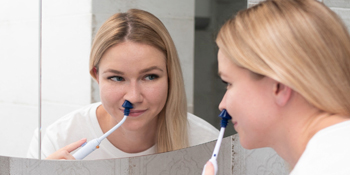smiling lady using the SinuPulse Elite to relieve allergy and sinus symptoms