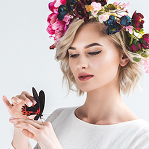 Serene woman with flowers and butterflies in her hair to highlight the inspiration for our jewely
