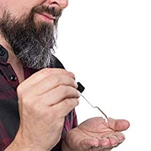 Image of man putting beard oil in palm using a dropper