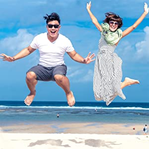 A male and female jumping on a warm beach scene