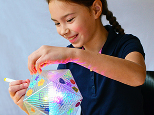 Girl decorating Party Lamp Kit plastic housing with erasable marker and reusable stickers and gems