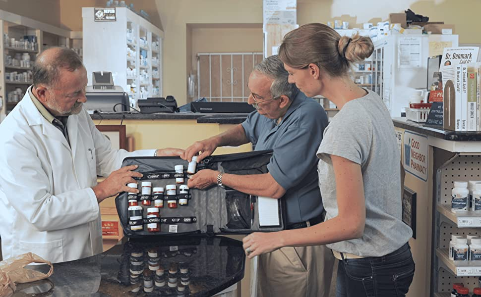 pharmacist doctor reviewing med management binder pill organizer with patient and caregiver