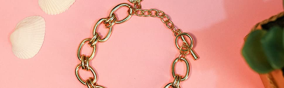 gold chain with gold toggle on pink background