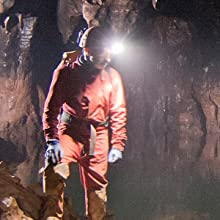 Cave explorer with a headlamp while standing on a rock