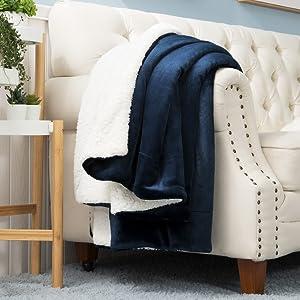 Bedsure Sherpa Fleece Blanket Navy lay on the sofa.