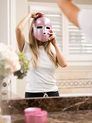Woman trying on HyperGlo by Lumiere Skyn in Bathroom Mirror. Docking Station is on a granite counter