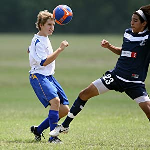 Two male teenagers playing soccer