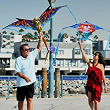 Man and woman playing with Wind n Sun Kites on the beach