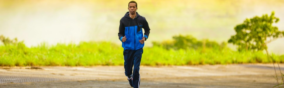 man jogging in blue workout gear with greenery behind him
