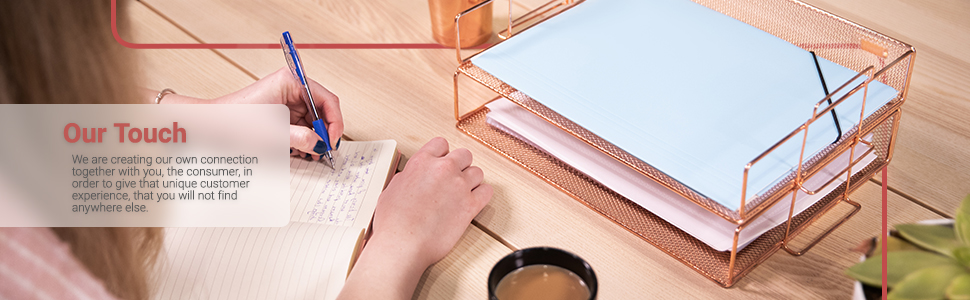 women writing in her notebook while drinking water next to her rose gold paper holder with notebooks
