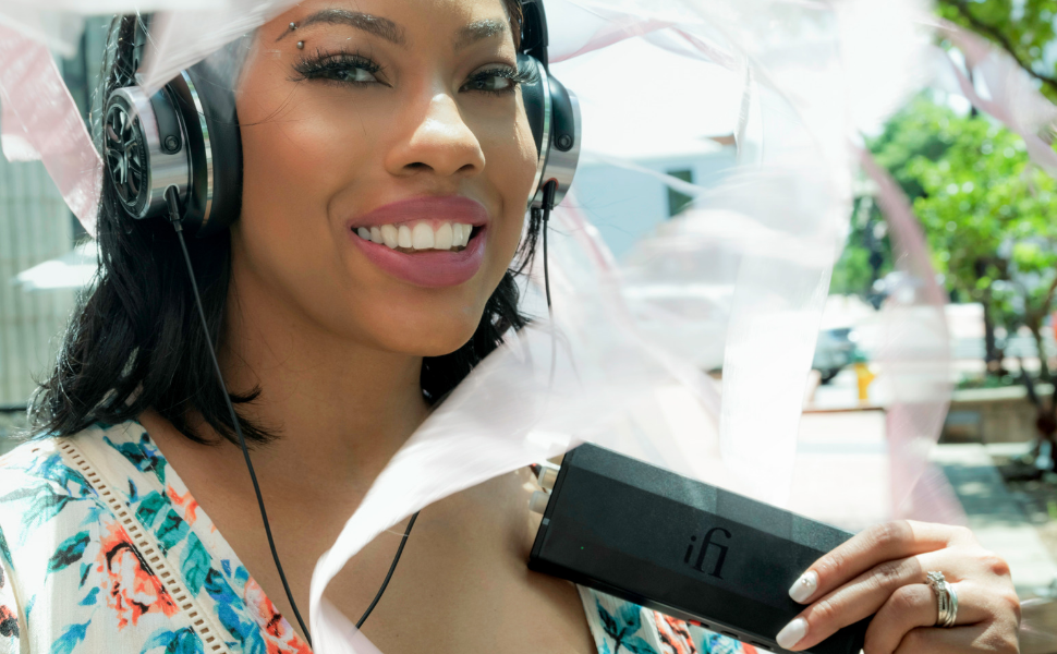 Woman smiling with micro iDSD Black Label and headphones
