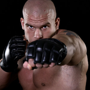 Muscular fighter, bald, shirtless wearing fingerless leather gloves, punching towards viewer