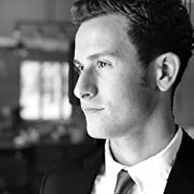 Attractive man wearing a suit and tie looking off into distance.