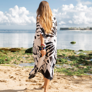 Woman on the beach wearing a black and white butterfly print long kaftan beach cover up maxi dress