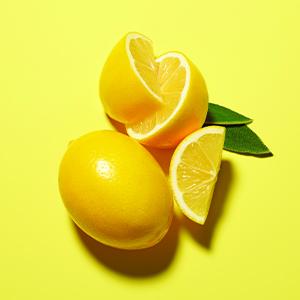 freshly sliced lemons against a yellow backdrop