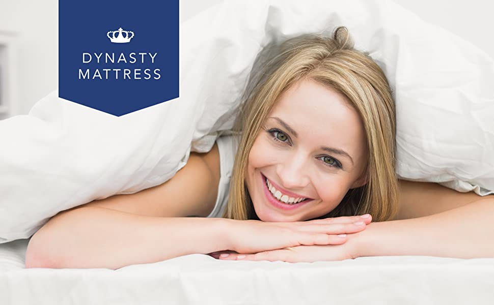 Woman smiling while lying in bed. Crown Dynasty Mattress logo on blue background in top left.