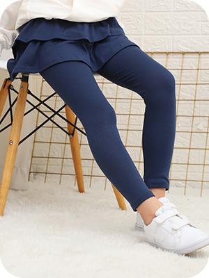 Una niña en leggings con falda ajustadas se sienta en una silla.