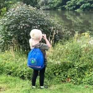 Girl with binoculars at lake
