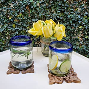 Two Cobalt Blue Rim Tumblers with water, rosemary and slices of lemon and lime in a garden setting